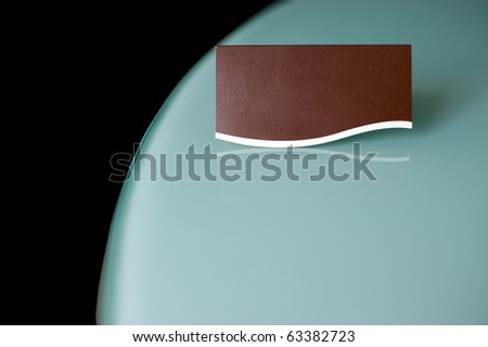 A blank brown business card on a curved reflective surface. - stock photo