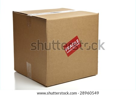 "A blank, brown, corrugated cardboard box or shipping box with a ""Fragile - Handle with Care"" sticker on a white background"