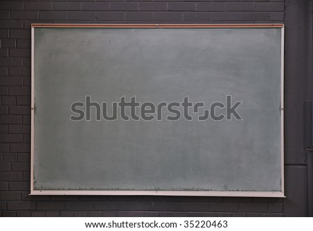 A blank chalk board against a brick wall in a gym - stock photo