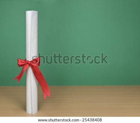 A blank chalkboard with a diploma on forefround. - stock photo