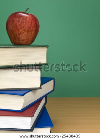 A blank chalkboard with an apple on top of a pile of books. - stock photo
