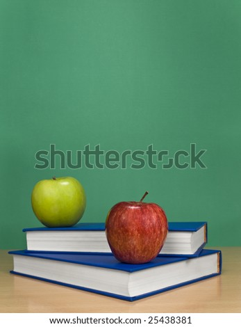 A blank chalkboard with apples over books.