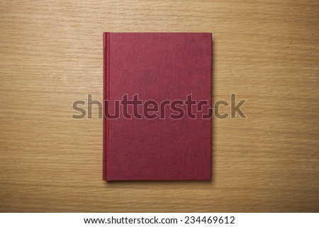 A blank(empty) red book(note, diary) cover on the wood desk(table), top view at the studio. - stock photo