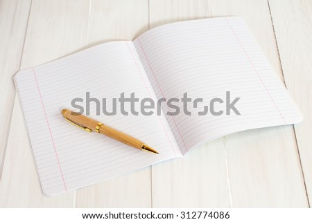 A blank exercise book jotter with pen - stock photo