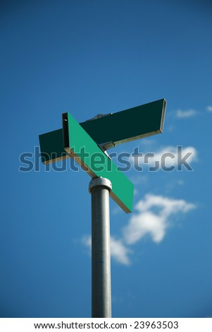 a blank green street sign against a blue sky outside