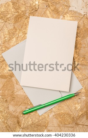 A blank greeting or invitation card alongside a green writing pen on layer of dried leaves for copy space. - stock photo