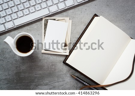 A blank notebook, computer keyboard, vintage photos and a cup of coffee - stock photo