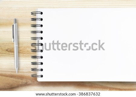 A blank notebook page and pen on wood office table, top view. - stock photo