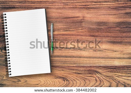 A blank notebook page and pen on wood office table. Top view with copy space. - stock photo