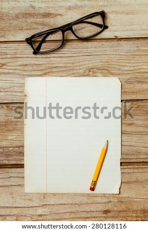 A blank old piece of paper on a wooden desktop with a pen and horn-rimmed glasses. - stock photo