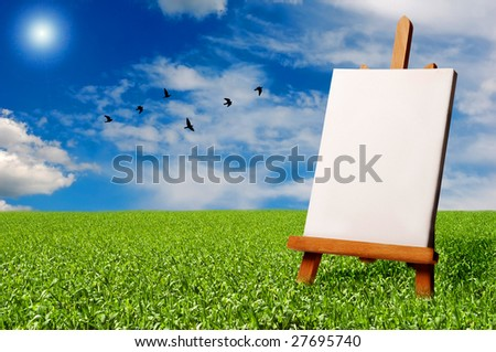 a blank painter easel in a meadow with a flock of birds flying in the sky - stock photo