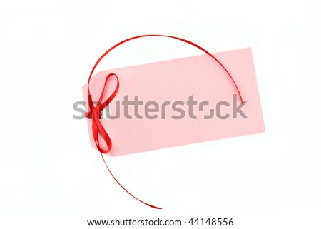 A blank pink tag with a pretty red ribbon on a white background with copy space.