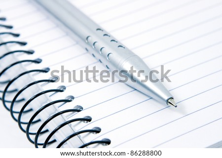 A blank ruled spiral note pad and pen ready for writing notes, reports, messages and letters for the student, office, writer, journalist or note taker - stock photo
