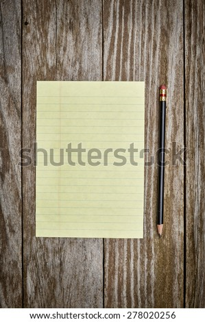 a blank sheet of paper with a black pencil on a wood background - stock photo