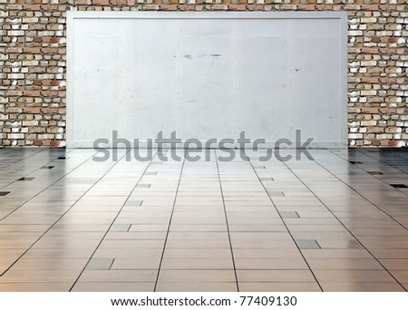 A blank white display board with space for text in a hall with brickwall in the background. - stock photo