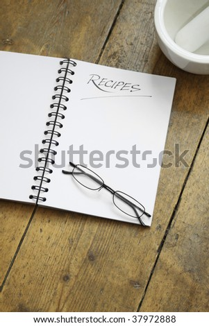 A blank wire spiral bound recipe book with the title 'recipe' hand written at the top of the page. A pair of black framed glasses rest on the page. Set on a wooden kitchen table top. - stock photo