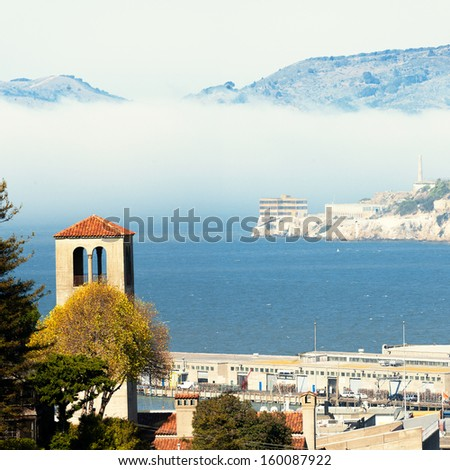 A blanket of fog rolls onto the San Francisco Bay behind Alcatraz Island - stock photo