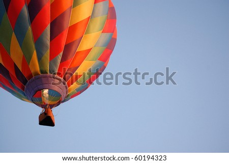 A blast of heated gas keeps a hot air balloon in flight - stock photo
