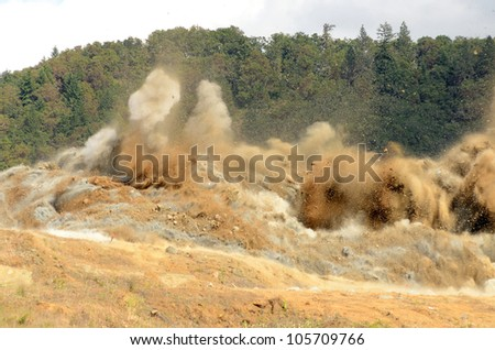 A blasting operation to remove a small hill in an airport expansion project in Oregon - stock photo