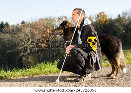 A blind man on a walk with his assistance dog  - stock photo