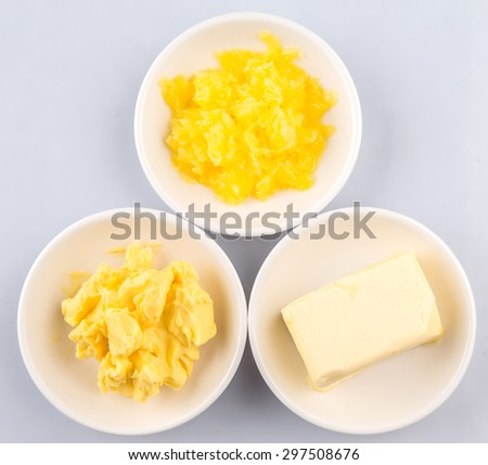 A block of butter, margarine and ghee in white bowls  - stock photo