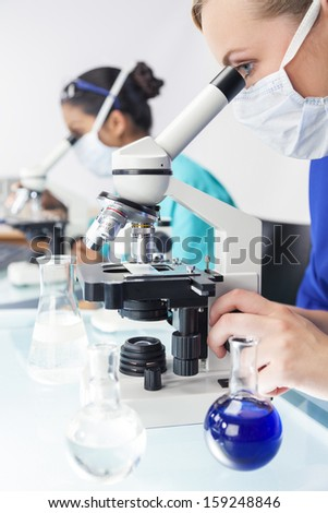 A blond female medical or scientific researcher or doctor using her microscope in a laboratory with her Asian colleague behind her.