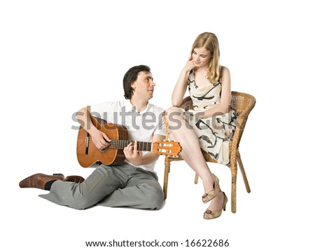 A blond girl and a man playing guitar for her - stock photo