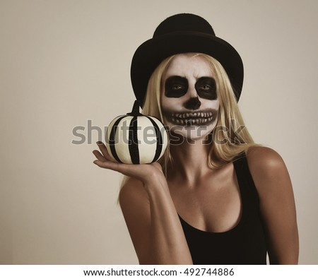A blond girl is wearing scary skeleton makeup paint on her face with copyspace. She is holding pumpkin decor for a Halloween message idea.