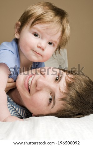 A blond-haired toddler lying on top of an older boy.