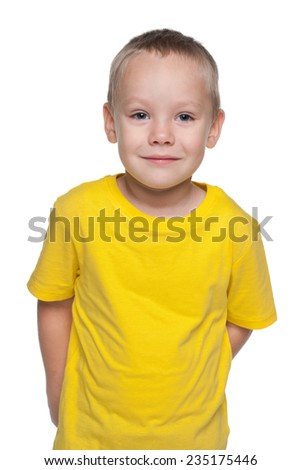 A blond little boy in a yellow shirt stands against the white background