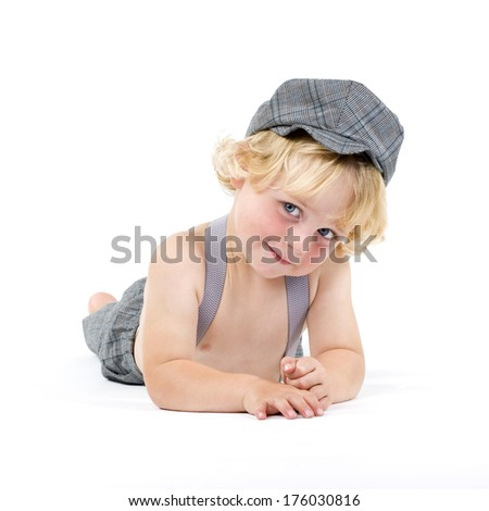 A blond little boy laying on the floor. - stock photo
