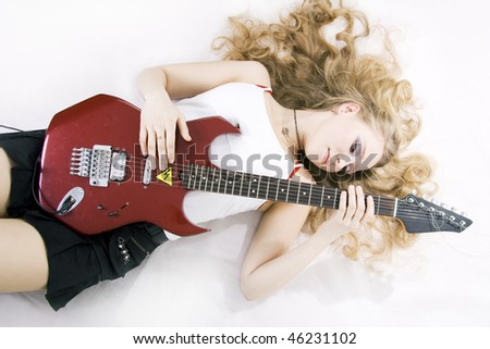 A blond long hair girl playing a red electric guitar and is lying on the floor. - stock photo
