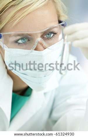 A blond medical or scientific researcher or doctor looking at a clear solution in a laboratory while wearing safety glasses and surgical mask - stock photo