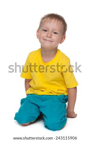 A blond preschool boy sits on the floor against the white background - stock photo