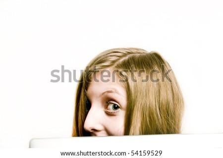 a blond teenager girl behind a screen with an impish look - stock photo