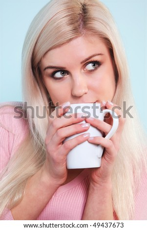 A blond woman drinking a mug of tea looking out of frame.