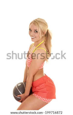 a blond woman holding on to a weighted medicine ball with a smile.