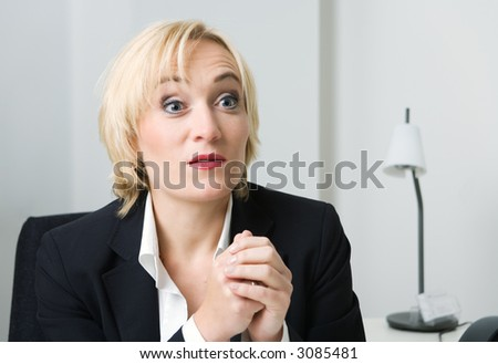 A blond woman in a suit listening