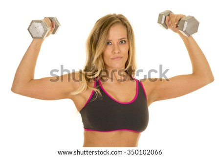A blond woman in her sports bra working out with her weights