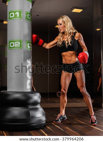 A blond woman in sexy sportswear boxing in a gym. - stock photo