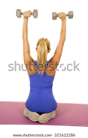 a blond woman working out with her weights, working out her shoulders - stock photo