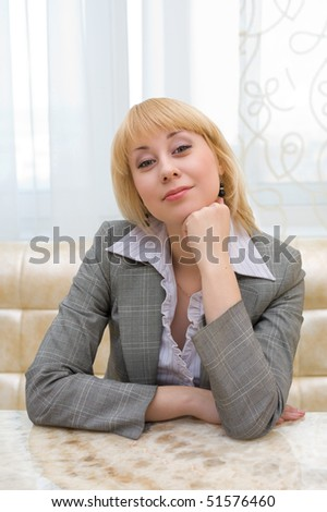 a blonde caucasian businesswoman sits at a restaurant table - stock photo