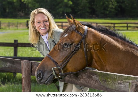 A blonde equestrian model poses in an outdoor environment - stock photo
