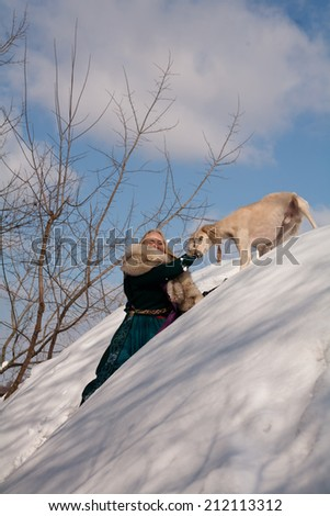 A blonde girl and a white saluki on snow  - stock photo