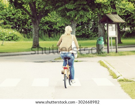 A blonde girl in a leather jacket is riding a bike in the streets on a summer day. Image has a strong vintage effect applied. - stock photo