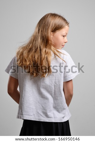 A blonde girl is hiding something. She is standing back and looking out of the corner of her eye on the gray background. - stock photo