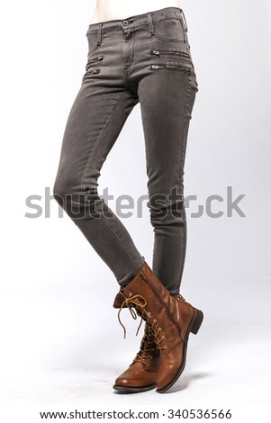 A blonde hair woman(girl, model) stand up wearing brown denim jean(pants, trousers) with black Military Shoes side view isolated white. - stock photo