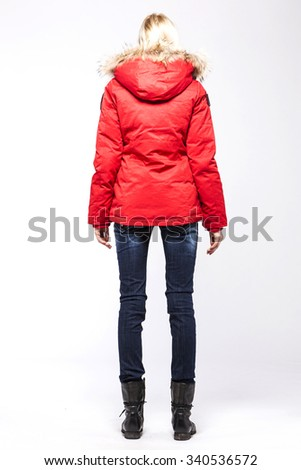 A blonde hair woman(girl, model) stand up wearing red down jumper and blue denim jean(pants, trousers) with hair back side view isolated white. - stock photo