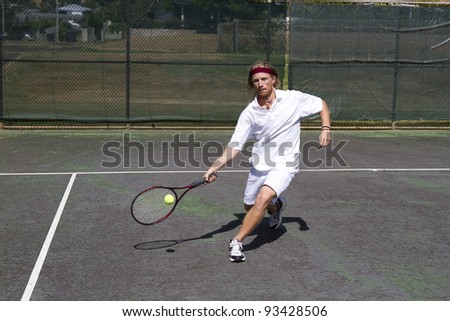 A blonde male tennis player takes a step into a solid forehand return swing - stock photo