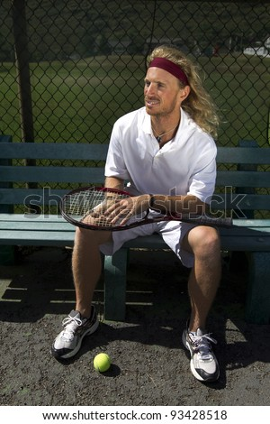 A blonde male tennis player waits his turn on the sideline bench - stock photo